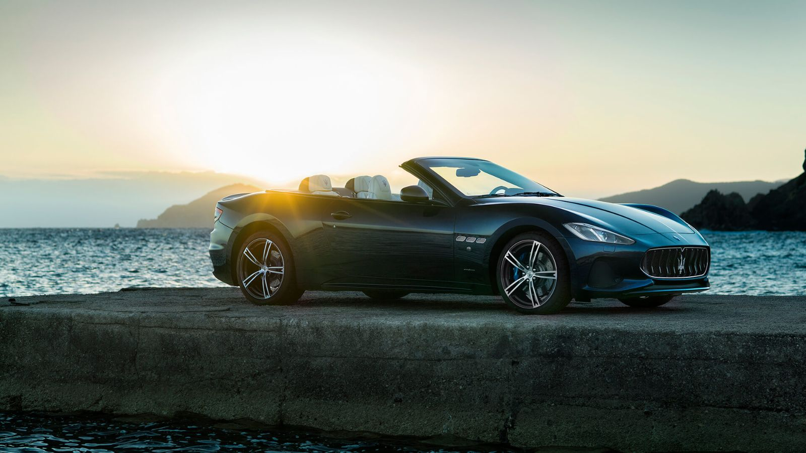 Black Gran Turismo Convertible - side view - seaside landscape